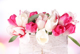 Beautiful tulips  in wooden box, on light background - 64192595