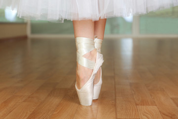 Ballerina legs in pointes in dancing hall