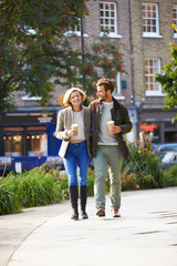Couple Walking Through Park With Takeaway Coffee