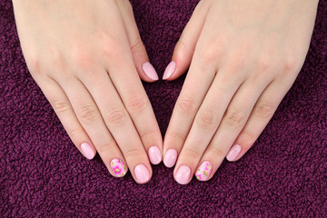 Beauty treatment, hands with painted fingernails at towel