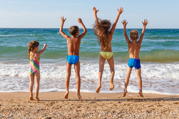 Four kids jumping on the beach
