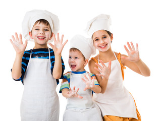 Three young chefs with hands in flour