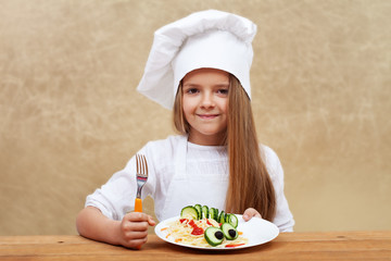 Happy child with chef hat and decorated pasta dish