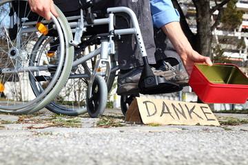 Bedürftiger Rollstuhlfahrer mit DANKE Schild