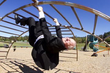 Businessman Upside Down in Playground