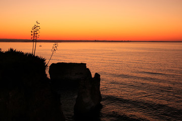 Silhouetted cliffs at sunrise, Ponta de Piedade, Lagos, Algarve,