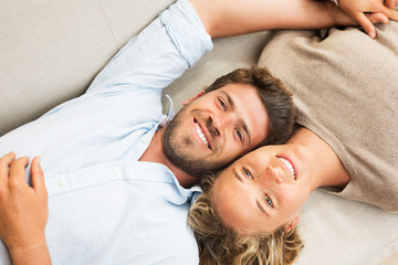 Happy young couple at home on sofa