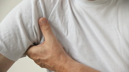 man scratches under his arm