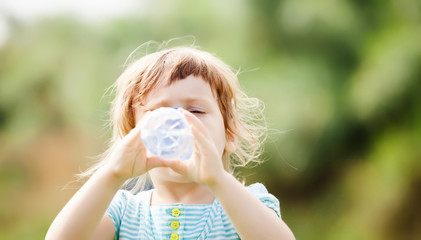 girl drinking from plastic bottle