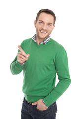 Junger lächelnder Mann in Grün zeigt auf etwas