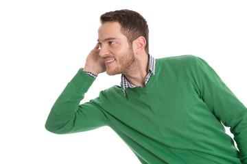 Junger Mann in Grün isoliert blickt lauschend zur Seite