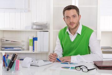 Deprimierter Geschäftsmann sitzend an seinem Schreibtisch