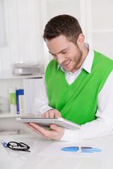Lachender Business Mann liest in seinem Tablet-PC