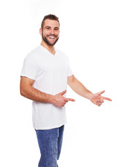 Happy young man in white tshirt showing empty copyspace