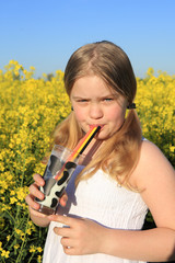 girl drinking milk with black red and yellow straws