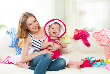 happy  Mother and baby girl with clothes ready for traveling on