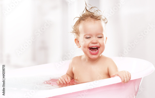 happy funny  baby  laughing and bathed in bath - 64208713