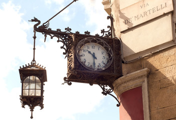 Old clock with lantern at Via de' Martelli Florence, Italy