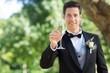 Smiling groom holding champagne flute in garden