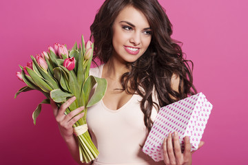 Beautiful young woman with spring bouquet and gift box