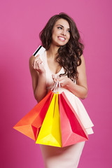 Smiling elegant female shopaholic on pink background
