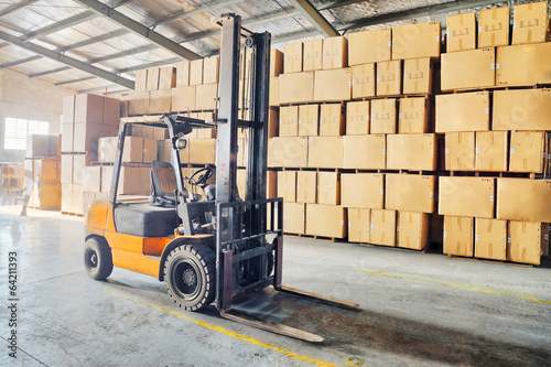 Large modern warehouse with forklifts - 64211393