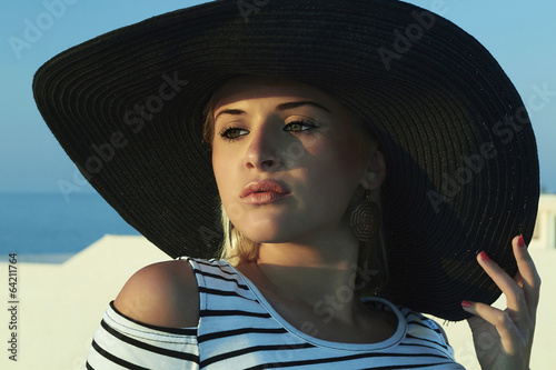 Beautiful woman in hat. On the Roof. Summer holidays. Blond girl
