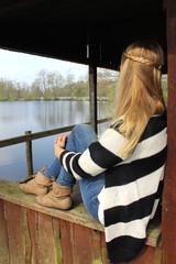 junge Frau schaut von Holzhütte auf den See