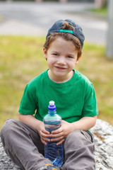 Little boy sit with bottle of water