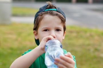 Little boy in cap drink water