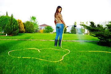 smiling woman is watering grass in her garden