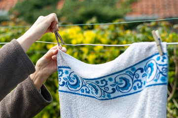 Old woman hanging laundry outdoor