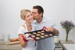 Man kissing woman's cheek as she holds freshly baked cookies in