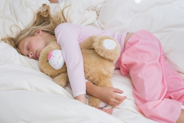 Girl sleeping peacefully with stuffed toy in bed