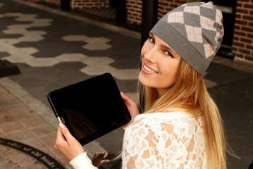 Young smiling blonde woman with tablet on city street