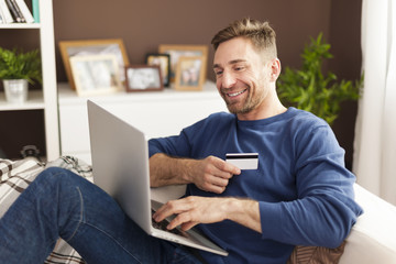 Smiling man during online shopping at home