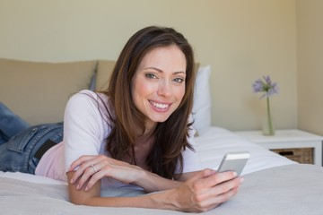 Smiling young woman text messaging in bed