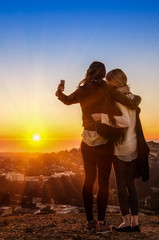 Couple of young women best friends taking a selfie at sunset