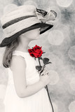 Young girl wearing an oversized hat holding a red rose