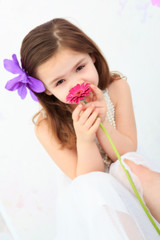 Young girl smelling a red flower