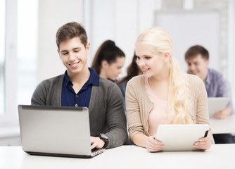 two smiling students with laptop and tablet pc
