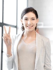 confident young woman showing v-sign