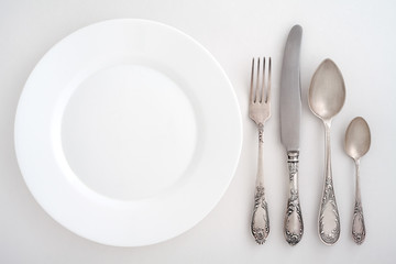 Vintage cutlery set with fork, knife, spoon and plate