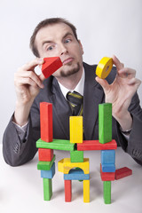 Businessman in the office plays toy's blocks