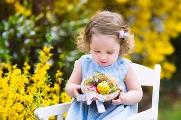 Beautiful curly toddler girl enjoying easter egg hunt in garden