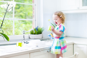 Cute little toddler girl in a colorful dress washing dishes