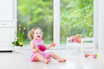 Little toddler girl playing tambourine in white nursery