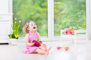 Cute curly toddler girl playing tambourine in sunny white room
