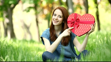 Young girh with shape heart in the park