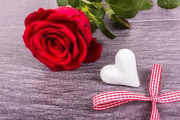 Rose mit Herz und karierter Schleife auf Steinboden